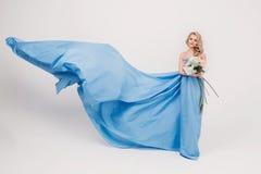 Härlig flicka i en blå lång klänning Arkivbild