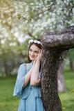 Härlig flicka i en blommande Apple fruktträdgård arkivbilder