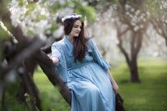 Härlig flicka i en blommande Apple fruktträdgård arkivfoto