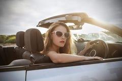 Härlig flicka i en flott bil fotografering för bildbyråer