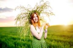 Härlig flicka i en grön klänning med kransen av lekmanna- blommor Royaltyfria Bilder