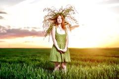 Härlig flicka i en grön klänning med kransen av lekmanna- blommor arkivfoto