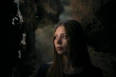 Härlig flicka i en grotta med en djup blick Arkivbild