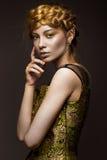 Härlig flicka i en guld- klänning med idérik makeup och flätade trådar på hennes huvud Skönheten av framsidan Royaltyfri Bild