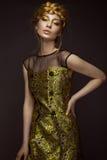 Härlig flicka i en guld- klänning med idérik makeup och flätade trådar på hennes huvud Skönheten av framsidan royaltyfria foton