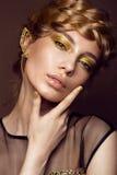 Härlig flicka i en guld- klänning med idérik makeup och flätade trådar på hennes huvud Skönheten av framsidan royaltyfri fotografi
