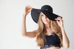 Härlig flicka i en hatt med ett brättemode Arkivbild