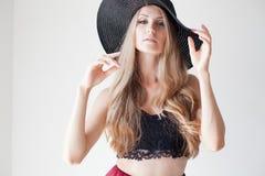 Härlig flicka i en hatt med ett brättemode royaltyfri bild