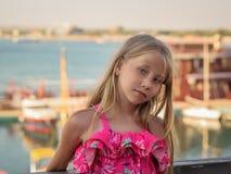 Härlig flicka i en härlig klänning på bakgrunden av hamnstaden i den sydliga staden arkivbild