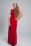 Härlig flicka i en lång röd klänning med det långa innehavet för lockigt hår Arkivbild