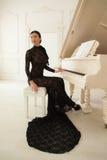 Härlig flicka i en lång svart klänning Fotografering för Bildbyråer