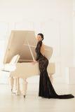 Härlig flicka i en lång svart klänning Arkivbilder