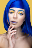Härlig flicka i en ljus blå peruk i stilen av cosplay och idérik makeup Härlig le flicka Långt exponeringsfoto som tas i en tunne Royaltyfri Bild