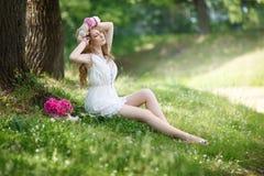 Härlig flicka i en ljus klänning och en krans av peons royaltyfria foton