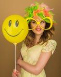 Härlig flicka i en ljus peruk och stora exponeringsglas som rymmer en ballong Royaltyfri Fotografi