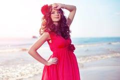 Härlig flicka i en ljus röd klänning vid havet Mot bacen royaltyfri fotografi