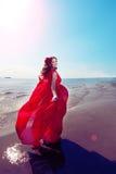 Härlig flicka i en ljus röd klänning vid havet Mot bacen arkivfoto