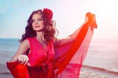 Härlig flicka i en ljus röd klänning vid havet Mot bacen royaltyfria foton