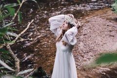 Härlig flicka i en mörk skog nära floden Arkivbild