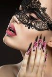 Härlig flicka i en maskering med långa fingernaglar Royaltyfri Fotografi