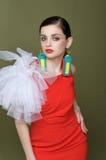 Härlig flicka i en röd klänning och örhängen från etiketter från koagulering Arkivbilder