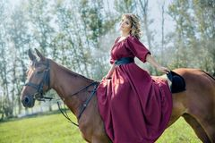 Härlig flicka i en röd lång röd klänning- och ridningahorse royaltyfri foto