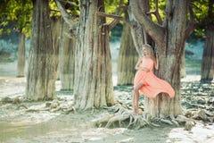 Härlig flicka i en rosa klänning i skogen Fotografering för Bildbyråer