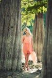 Härlig flicka i en rosa klänning i skogen Arkivbild