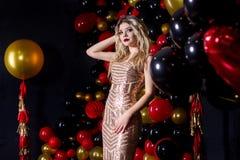 Härlig flicka i en sexig klänning på en studio i en ballonsbakgrund royaltyfria bilder