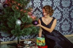 Härlig flicka i en smart klänning nära jul royaltyfria foton