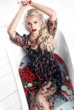 Härlig flicka i en sommarklänning i badrummet med blommor Härlig le flicka royaltyfri foto