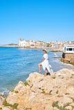 Härlig flicka i en sommarklänning och hatt på kusten nära en gammal stad Europa för bakgrund Medelhav Sitges Arkivbild