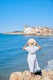 Härlig flicka i en sommarklänning och hatt på kusten nära en gammal stad Europa för bakgrund Medelhav Sitges Royaltyfria Foton