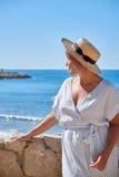 Härlig flicka i en sommarklänning och hatt på kusten nära en gammal stad Europa för bakgrund Medelhav Sitges Royaltyfri Bild
