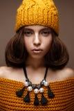 Härlig flicka i en stucken hatt på hennes huvud och en halsband av pärlor runt om henne hals Modellen med försiktigt smink och gu fotografering för bildbyråer