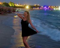 Härlig flicka i en svart klänning vid havet arkivbilder