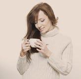 Härlig flicka i en tröja med en kopp Royaltyfri Foto