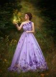Härlig flicka i en ursnygg purpurfärgad lång klänning som rymmer en stearinljus arkivfoton