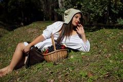 Härlig flicka i en vit blus, en hatt som vilar på gräsmattan Fotografering för Bildbyråer
