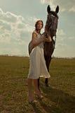 Härlig flicka i en vit kappa med hästen Royaltyfri Bild