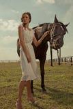 Härlig flicka i en vit kappa med hästen Arkivfoto