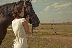 Härlig flicka i en vit kappa med hästen Arkivbilder