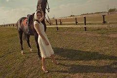 Härlig flicka i en vit kappa med hästen Arkivfoton