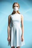 Härlig flicka i en vit klänning med en respiratorisk maskering på hennes framsida fotografering för bildbyråer