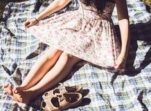 Härlig flicka i ett klänningsammanträde utomhus i solljuset barfota Arkivfoto