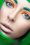 Härlig flicka i ett ljust - grön peruk i stilen av cosplay och idérik makeup Härlig le flicka Långt exponeringsfoto som tas i en  Royaltyfria Foton