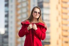 Härlig flicka i ett rött lag och exponeringsglas på bakgrunden av huset Arkivbilder