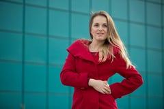 Härlig flicka i ett rött lag och exponeringsglas på bakgrunden av huset Royaltyfri Fotografi
