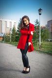 Härlig flicka i ett rött lag på en parkeragränd arkivbilder