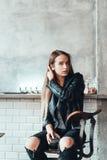Härlig flicka i ett svart omslag i ett kafé royaltyfri bild